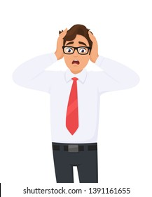 Shocked/amazed young business man holding hands on head and keeping mouth open. Headache pain or stress. 