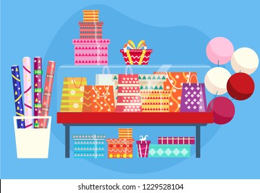 Showcase with gift bags, present boxes, rolls of wrapping paper and baloons.
