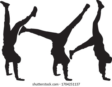 Silhouette of agile young man doing a handstand.