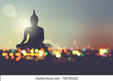 Silhouette buddha on Abstract blur bokeh in night city background