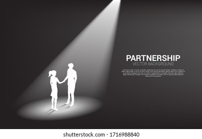 Silhouette of businessman and businesswoman handshake in spotlight. Concept of team work partnership and cooperation.