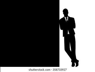 Silhouette of a businessman leaning at black blank space for copy with arm crossed