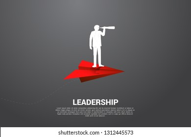 Silhouette of businessman looking through telescope on red origami paper airplane. Business Concept of leadership and vision mission.