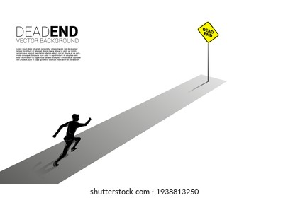 Silhouette businessman running to the end of road with dead end signage . Concept of wrong decision in business or end of career path.
