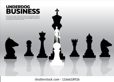 Silhouette of businessman standing on white pawn chess piece in front of all of black chess piece . Concept of underdog business marketing strategy.