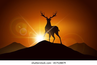 Silhouette of deer on a mountain peak against sunset landscape.