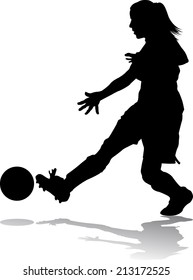 Silhouette of a girl soccer player kicking the ball.