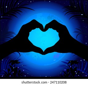 Silhouette of hands making a heart on a background of the night sky and the moon.
