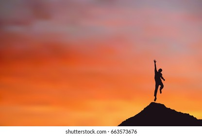 Silhouette of happy man jumping on Mountain cliff looking at sunset sky background