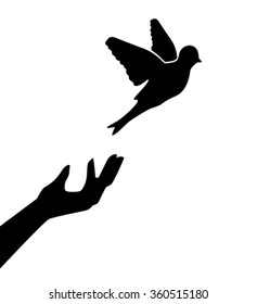Silhouette of the human hand, which releases the bird and the bird flies