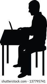 A silhouette of a man sitting at a laptop computer