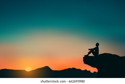 Silhouette of man sitting on Mountain cliff looking at sunset sky background
