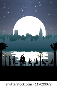 Silhouette of people eating outdoor by the river at night with cityscape background