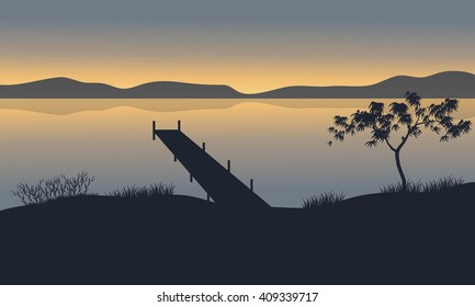 Silhouette of pier in lake at the sunset