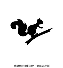 A silhouette of a squirrel sitting on a branch.