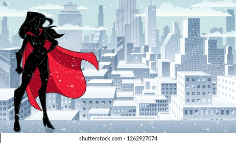 Silhouette superheroine standing tall against city background in winter.