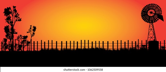 silhouette of wind mill in the outback with bright orange sunset