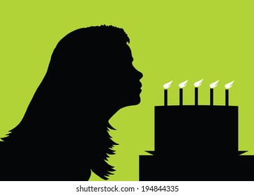 A silhouette of a woman blowing out her birthday candles.
