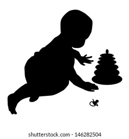 The silhouettes of the child 0-1 year, playing with the pyramid.