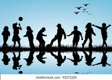 Silhouettes of children playing near a water