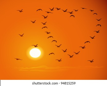 Silhouettes of flying flock birds (in shape of heart) against a sunset and the orange sky.