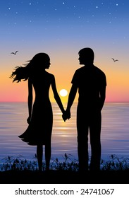 Silhouettes of man and woman standing and holding hands at evening time.  On the background sunset and stars over the sea.