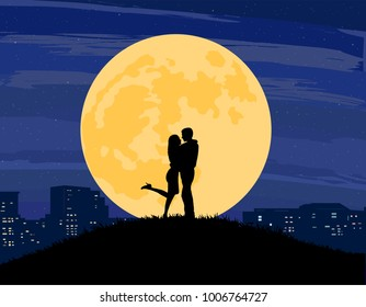 Silhouettes of a man and woman standing and kissing on a hill of grass with a big full moon, city skyline, and dark sky in the background.