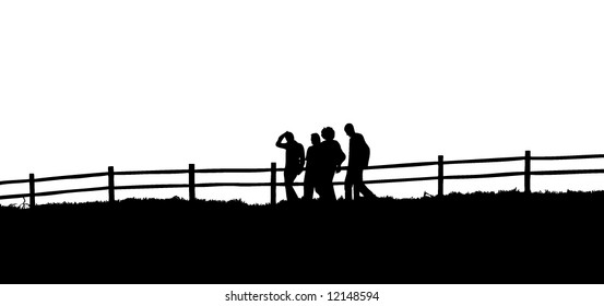 Silhouettes of people walking in front of a fence