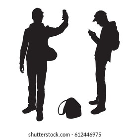 Silhouettes of a teenager taking pictures of himself on a smart phone sending a message, black color, isolated on a white background