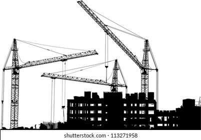 Silhouettes of three cranes working on the building