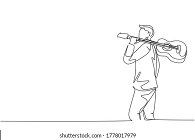 Single continuous line drawing of young happy male guitarist walking while carrying acoustic guitar oh his shoulder. Modern musician artist performance concept one line draw design vector illustration