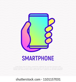 Smartphone in hand thin line icon. Modern vector illustration.