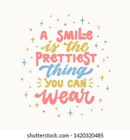 A smile is the prettiest thing you can wear. Iinspirational hand drawn lettering quote. In bright blue, pink, yellow colors. Motivational phrase. T-shirt print, poster, postcard, banner design. Female
