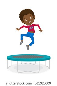 Smiling black boy wearing blue jeans and a red t-shirt jumping on a trampoline.