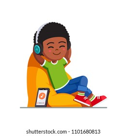 Smiling boy kid sitting on bean bag chair listening to music enjoying song with wireless headphones. Smiling kid using phone music app relaxing. Wireless technology. Flat vector isolated illustration