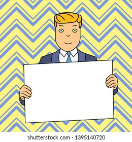 Smiling Man in Formal Suit Holding Big Blank Poster Board in Front of Himself with Both Hands. Creative Background Space for Announcements and Promotions