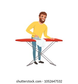 Smiling man ironing clothes on an ironing board. Cartoon house husband. Young guy in yellow sweater and blue jeans. Housekeeping theme. Flat vector design