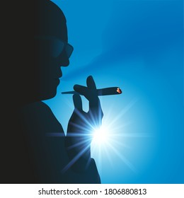 Soft drug addiction concept, with the backlit silhouette of a man smoking a joint of cannabis.