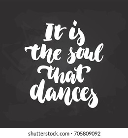 It's the soul that dances - lettering dancing calligraphy quote drawn by ink in white color on the black chalkboard background. Fun hand drawn lettering inscription