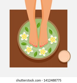 Spa foot therapy. Women's feet in bowl with flowers and leaves