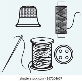 Spool with threads, sewing button and thimble isolated on blue background
