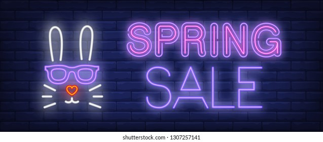 Spring sale neon text with rabbit head. Spring sale advertising design. Night bright neon sign, colorful billboard, light banner. Vector illustration in neon style.