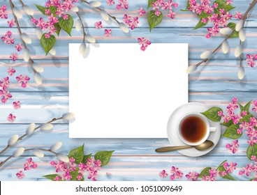 Spring top view wooden background with a cup of tea, flowers, blank piece of paper and pussy willow branches