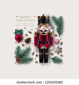 Square Christmas Composition Made of Nutcracker, Pine Branches, Fir-Cones, Candy and Glitter Snowflake. Flat lay, top view.