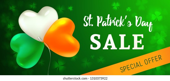 St Patrick's Day Sale. Glossy heart-shaped balloons painted in the colors of the Irish flag. Blurred background with leaves of shamrock. Design concept for advertising banner, poster or flyer.
