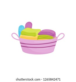 Stack of clean folded linens and towels in purple plastic basket. Laundry and housework theme. Flat vector design