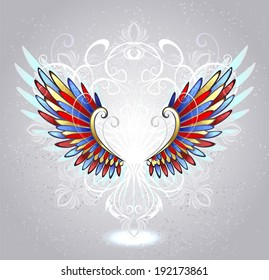 Stained glass wings of red, blue and yellow glass, decorated with white pattern on light background.