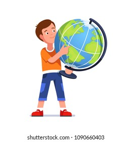 Standing boy holds big desktop terrestrial globe in hands. Kid looking & pointing index finger at geographical location. Smiling school student learning geography. Flat vector character illustration