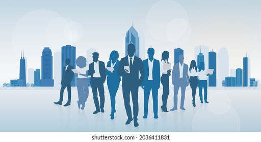 Standing group of business people silhouette with laptops. Over city landscape modern office buildings.