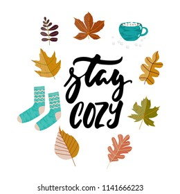 Stay cozy - hand drawn Autumn seasons holiday lettering phrase and Hugge doodles with leaves, cup of tea, cocoa, chocolate, warm socks isolated on white. Ink illustration for banners, cards, posters
